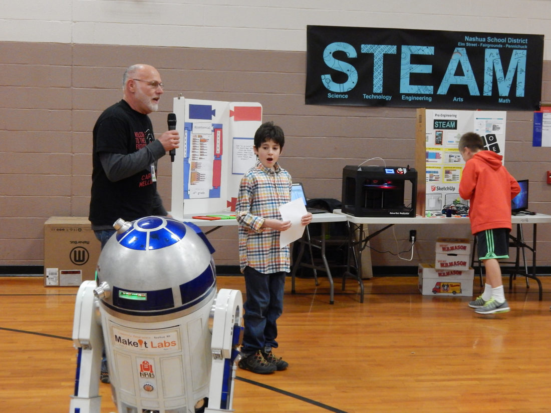 Staff Photo by TINA FORBES From left, Elm Street Middle School pre-engineering teacher David Purington and Bicentennial Elementary School student Beckett Lutton introducing Beckett's calculator app at the STEAM fair Thursday night.