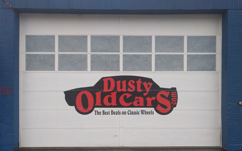 Staff photo by DAMIEN FISHER One of the several garage doors at Dusty Old Cars on Airport Road.The company's warehouse contains close to 400 vehicles.