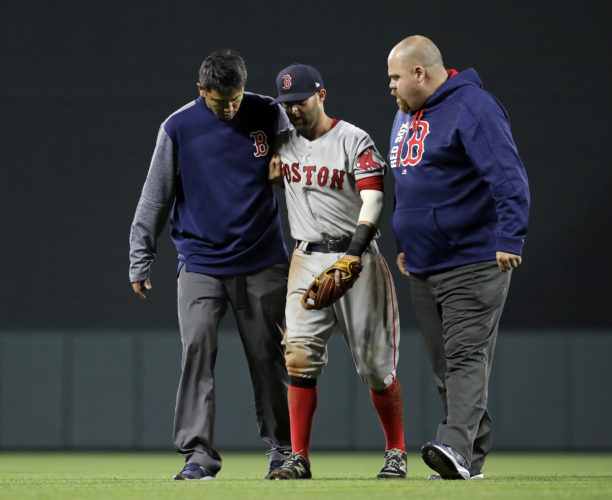 Boston Red Sox second baseman Dustin Pedroia, center, is assisted off the field after being injured during the eighth inning of the team's baseball game against the Baltimore Orioles in Baltimore on Friday. (AP Photo/Patrick Semansky)