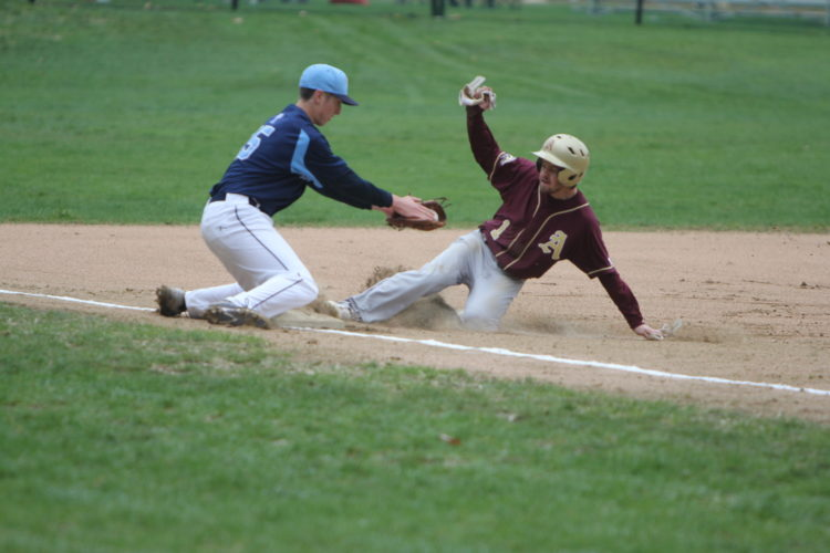 Staff photo by TOM KING Alvirne's Pat Rauseo steals third ahead of the tag by Nashua North's Colton Welch during the Titans' 3-0 win over the Broncos on Saturday in Hudson.