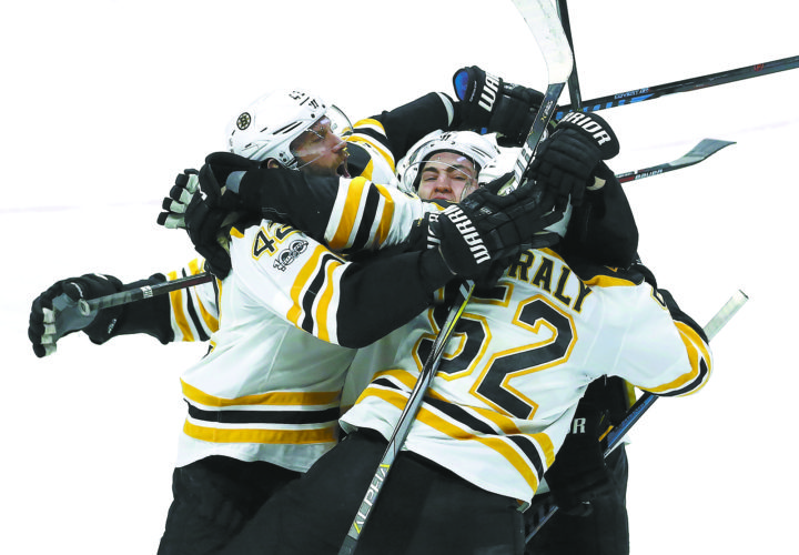 Boston Bruins swarm teammate Sean Kuraly (52) to celebrate his goal against the Ottawa Senators during the second overtime of Game 5 of a first-round NHL hockey Stanley Cup playoff series Friday in Ottawa, Ontario. (Fred Chartrand/The Canadian Press via AP)
