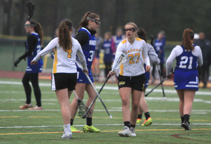Staff photo by Jason Orfao/Souhegan's Sammi Jay (27) celebrates with Savannah Benn (4) during the Sabers' 18-2 rout of Salem on Friday at Calvetti Family Field.