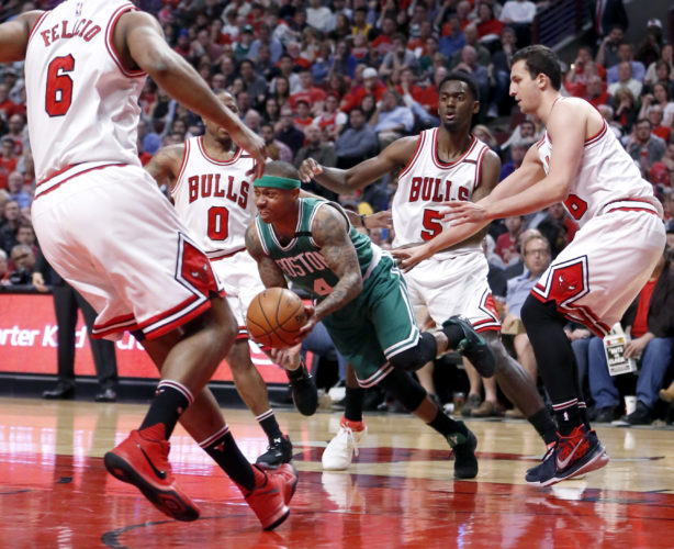 Boston Celtics' Isaiah Thomas (4) dribbles through the Chicago Bulls defense of Cristiano Felicio (6) Isaiah Canaan (0) Bobby Portis (5) and Paul Zipser during the first half in Game 4 of an NBA basketball first-round playoff series in Chicago on Sunday. (AP Photo/Charles Rex Arbogast)