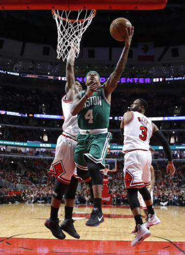 Boston Celtics' Isaiah Thomas (4) scores past Chicago Bulls' Jimmy Butler, left, and Dwyane Wade (3) during the second half in Game 3 of an NBA basketball first-round playoff series in Chicago, Friday, April 21, 2017. The Celtics won 104-87. (AP Photo/Charles Rex Arbogast)