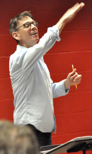 Photo courtesy of JOHN HERPER Dan Perkins is shown conducting a rehearsal of the Manchester Choral Society for its upcoming Candide concerts Saturday and Sunday at the Dana Center of Saint Anselm College in Manchester.