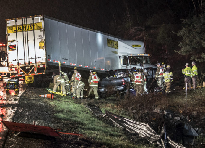 Photo by Jeffrey Hastings Manchester firefighters work to extricate Merrimack resident Derrick Vossbrink from his pickup truck while another crew shores up the tractor-trailer unit after the vehicles collided near Interstates 293 and 93 in Manchester Tuesday night.