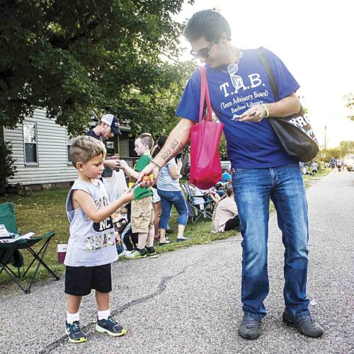 Photo by Janelle Patterson Mike Hubbard, of Georgia, hands Ty Hart, 4, of Deerwalk, a toy during the Barlow Fair Parade Friday.