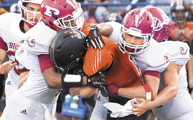 Photo by Jeff Baughan Marietta's Dominic Vanfossen runs into Parkersburg's Brenton Strange, left, and Davey McNemar during the Tigers' 49-13 victory over the Big Reds.