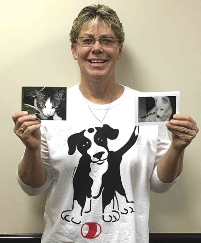 Photo by Brett Kline Kim Davis of Parkersburg holds two sets of custom made cards that she sells. Each card has non-staged photos of animals she has encountered over the years.
