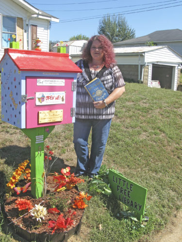 "Photos Provided Saundra McGary Eaton stands by her Little Free Library in front of her home at 811 28th St. in Vienna, holding the book ""The Shepherd's Crown"" by author Terry Pratchett. The Eaton little library is having a grand opening from 1-3 p.m. Oct. 15."