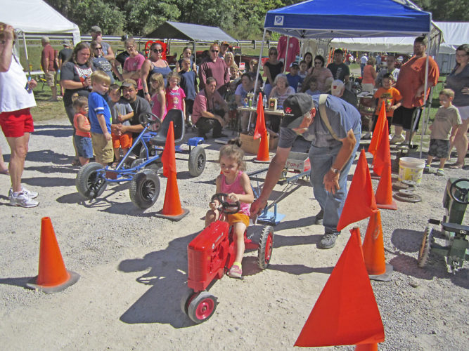 Photo by Wayne Towner Jazmyne Persinger, 4, of Ritchie County, competed Sunday in the kiddie tractor pulls at Mountwood Park on the final day of the Volcano Days Antique Engine Show and Festival.
