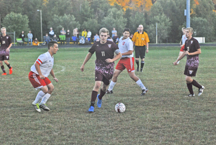 Photo by Matthew Hale  Senior midfielder Josh Folwell of Williamstown dribbles against Ravenswood, as the Red Devils' Bradley Parker tries to catch up. Folwell scored two goals as the 'Jackets prevailed, 6-1.