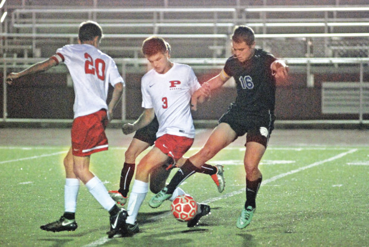 Photo by Joe Albright  Parkersburg's Parker Miller works against Riverside defenders Tuesday during the Big Reds' 7-0 win over the Warriors. Miller scored two times for victorious Parkersburg.