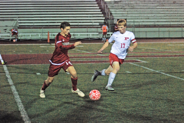 Photo by Matthew Hale Parkersburg's Jack Johnson (17) battles Hurricane's Ryan Fisher for the ball during a high school soccer match Thursday at Stadium Field. The match resulted in a 2-2 draw.