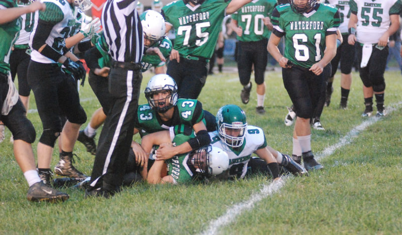 Photo by Mike Morrison Waterford's Braden Bellville, center, recovers a fumle during a high school football game Friday against Eastern.