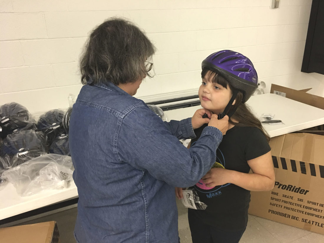 Photo by Michael Erb Toni Tiano, left, with the Mid-Ohio Valley Regional Highway Safety Program, fits a bike helmet on third-grader Kayla Rodriguez, right, during a safety event Friday at Franklin Elementary Center.
