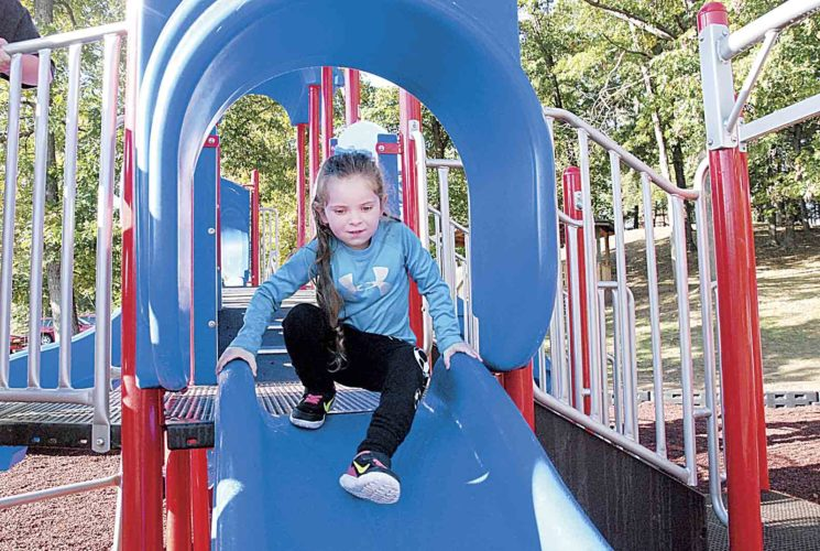Photo by Evan Bevins Parkersburg resident Annabelle McCrady, 5, gets ready to use one of the slides on the recently installed playground equipment at Southwood Park Friday. City officials held a ribbon-cutting for the equipment Friday morning.