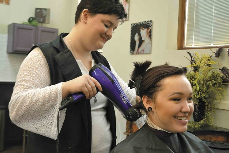 Photo by Breckin Wells Students Shayana Glenening, 19, of New Martinsville and Alaina Smendzuick, 18, of Whipple, experiment with hairdos at the new Artisan School of Cosmetology in Marietta.
