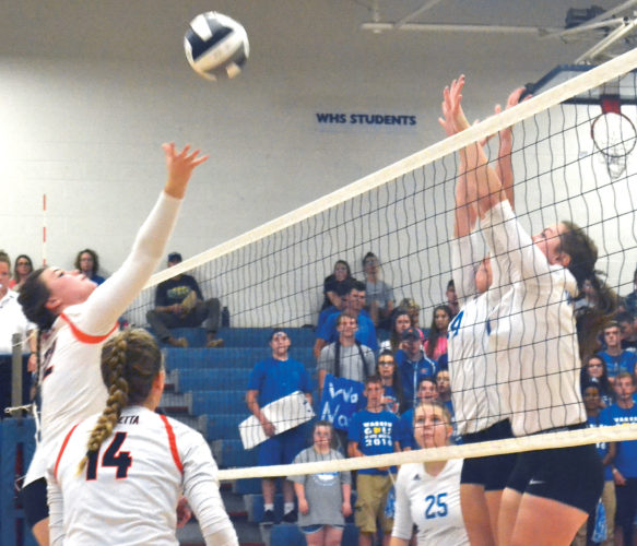 Marietta's Alexis Palazzo, left, tips the ball over the net during a high school volleyball match against Warren Wednesday in Vincent. Marietta won in three sets. Photo by Ron Johnston.