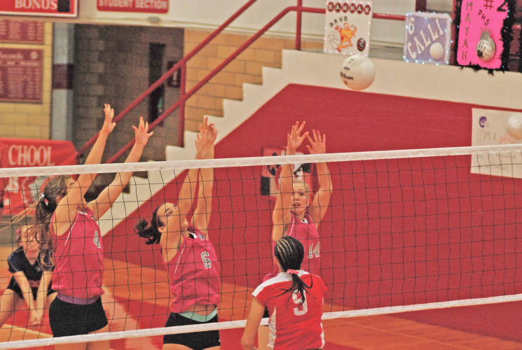 From left, Roane County's Kayla Strickland, Lauren Gorman and Cailyn Reynolds attempt a triple block against the spike from Parkersburg's Shay-Lee Kirby in a match earlier this year inside Memorial Fieldhouse. Photo by Jay W. Bennett