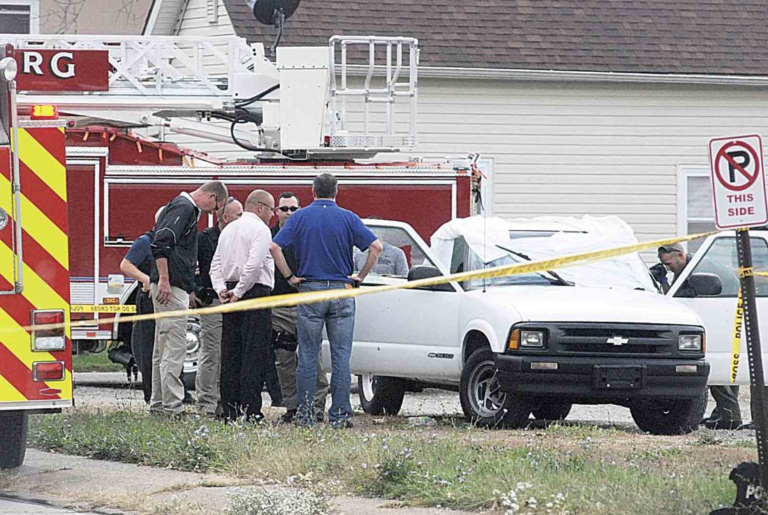 From left, Parkersburg Police Sgt. J.M. Stalnaker, Lt. G.D. Nangle, Chief Joe Martin, Detective D.D. Sturm and Wood County Prosecutor Jason Wharton confer at the scene of a double suicide on Neal Street behind O'Reilly Auto Parts Wednesday afternoon as Detective K.S. Barnette, right, photographs the truck in which the individuals shot themselves. (Photos by Evan Bevins)