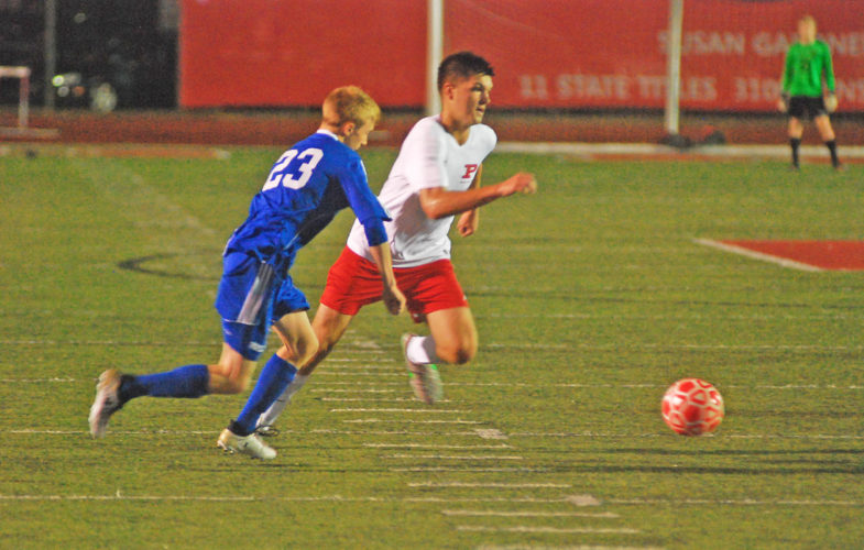 Parkersburg's Parker Miller works against Ripley defender Kaegun Jackson Thursday during the Big Reds' 4-1 Class AAA Region IV, Section I finals win over the Vikings at Stadium Field. Miller scored a goal and assisted on another in the second half. Photo by Joe Albright.