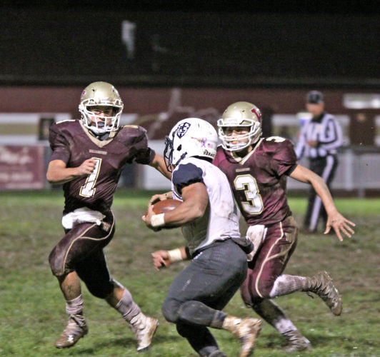 Trenton Tallman (1) and Carter Haynes (3) of Williamstown close in on Ryan Roedersheimer of Parkersburg Catholic in the Yellowjackets' 41-12 homecoming night win on Friday. Photo by Michael Uhl.