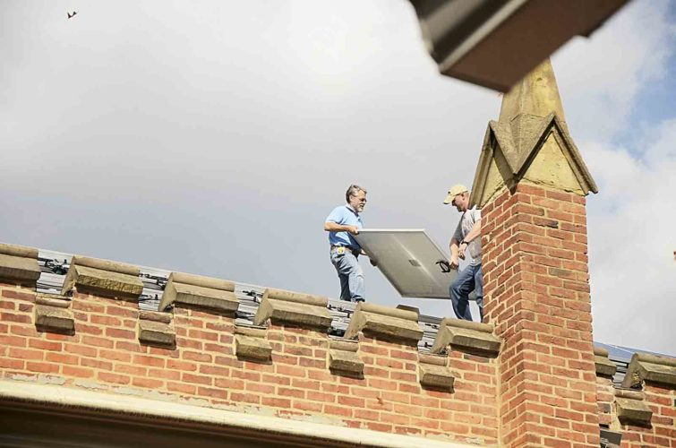 Chip Pickering, owner of Pickering Associates of Parkersburg, and Jeff Burge, electrician with Pro 1 Electric, LLC, work on installing the solar panels on the roof of the First Unitarian Universalist Society of Marietta on Tuesday. (Photo by Hannah Kittle)