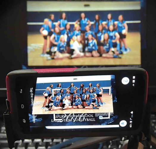 Ann Nester shows how the Live Portrait app works with a photo of the Ripley High School Volleyball team. When a smartphone is held up to the photo, a video plays of the players. (Photo by Jeff Baughan)
