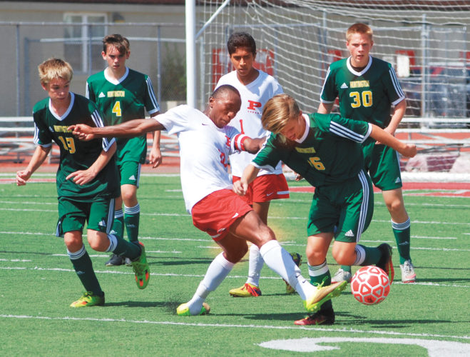 Parkersburg's Immanuel Opoku-Duah (10) battles for possession of the ball with Huntington's Owen Stoll (16) while teammates of both competitors look to help during the Big Reds' 5-0 win over the Highlanders earlier this season. Photo by Steve Hemmelgarn.