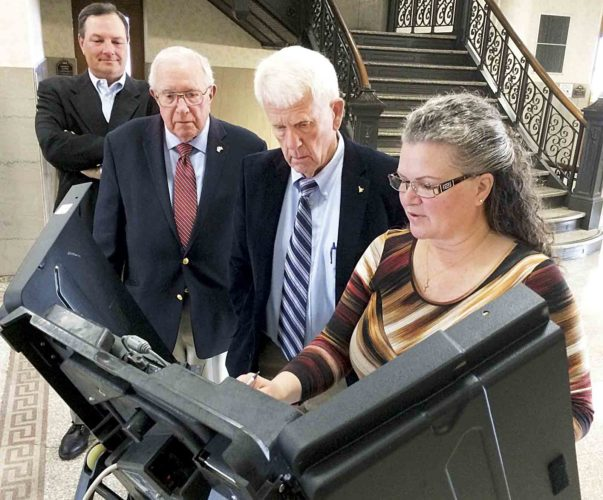 Melody Ross, far right, of the Wood County Clerk's office tests one of the voting machines for Wood County Commissioners Steve Gainer, Bob Tebay and Blair Couch. (Photo by Brett Dunlap)