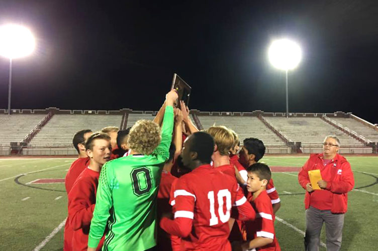 Parkersburg boys soccer holds up the West Virginia Class AAA, Region I championship plaque after downing Hurricane 3-1 Thursday night to advance to the state tournament in Beckley. Photo by Joe Albright.