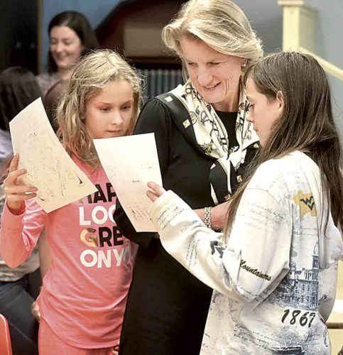 "Photo by Jeff Baughan U.S. Sen. Shelley Moore Capito, R-W.Va., receives papers from fifth grade girls at McKinley Elementary School at the conclusion of Capito's ""West Virginia Girls Rise Up!"" presentation in the school's library."