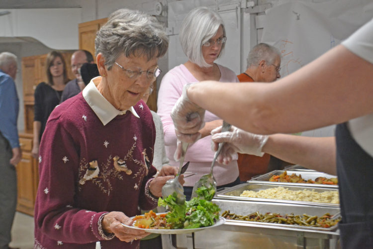 "Photo by Breckin Wells On Sunday, Patti Woodford receives her dinner, catered by Joe Mamma's Kitchen, before the film ""God's Not Dead"" at St. John's Evangelical Church in Lowell."