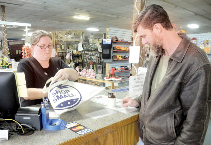 Photo by Jeffrey Saulton Crystal Walters, left, an employee at Peddlers Junction in Belpre, checks out a purchase by Tom Donahue, of Belpre, during Shop Small Saturday.