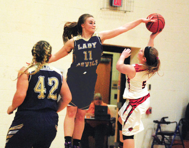 Photo by Jay W. Bennett Wirt County's Caitlin Cottrell has a runner in the lane blocked by St. Marys' Jordan Fox (11) as Blue Devil teammate Samantha Maidens (42) looks on Tuesday night in Elizabeth. The Blue Devils knocked off the Tigers, 85-33.