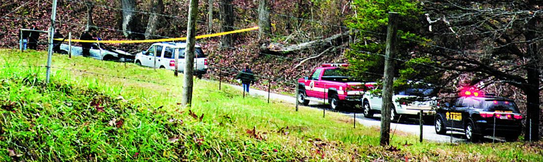 Photo by Evan Bevins Investigators survey the scene of a car fire on Badgley Fork Road in Mineral Wells Thursday morning. A body was found in the car and sent to the West Virginia Medical Examiner's Office for an autopsy and identification.