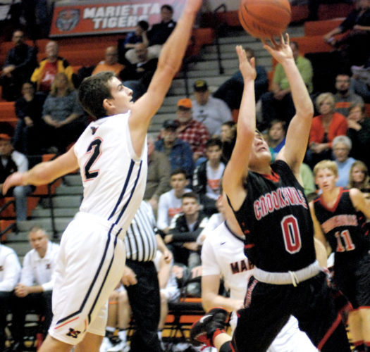 Marietta's Turner Hill (2) blocks the shot of Crooksville's Mike Baughman (0) during a high school basketball game Friday night at Sutton Gymnasium. Photo by Jordan Holland.