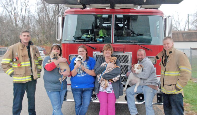 Photo by Evan Bevins Parkersburg firefighter Adam Delbaugh, from left, Humane Society of Parkersburg kennel tech Sheri Schwartz, holding Fancy Pants; adoption counselor Ashlie Ferrell, holding Martin, a rabbit; manager Amber Dennison, holding Layla; kennel tech Scott Little, holding Luna Moon; and Parkersburg firefighter Brett Ullman pose for a photo outside the HSOP shelter Friday. The Parkersburg Fire Department is holding a pet food and supplies drive for the shelter from Dec. 5-23.