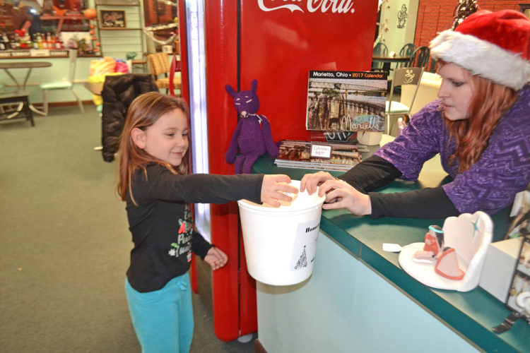 Photo by Peyton Neely Brooklyn Garrett, 4, of Little Hocking, picks out a snowball for a discount at Silver Linings on Front Street during the Merry-Etta Moonlight Savings Sale on Friday evening.