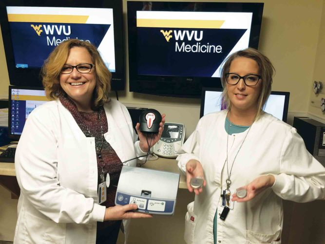 Photo by Brett Dunlap WVU Medicine Camden Clark Medical Center Cardiac Device Clinic Staff Nurse Kristi Nicholson holds an adapter that allows home heart monitoring devices that were traditionally plugged into a landline phone system to operate using cell phone signals whether the patient has a cell phone or not and Staff Nurse Mysti Carpenter holds a pacemaker and an implantable cardioverter defibrillator. The clinic is starting to transition people to new technologies in their monitoring as indications seem to indicate traditional landline phone systems will be phased out in the coming years.