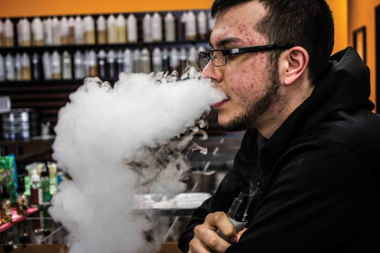 Photo by Janelle Patterson Tyler Morris, 21, of Marietta, blows vapor at Freedom Vapor.