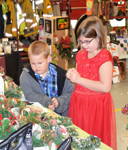 Photo by Doug Loyer McKensie Mason, 7, right, and brother Devon Mason, 5, both of Marietta look at some items at the Barlow VFD Craft Show.