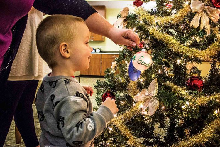 Aden Karcher, 2, of Marietta, hangs an ornament in honor of his grandmother at Strecker Cancer Center in Marietta on Monday. (Photo by Janelle Patterson)
