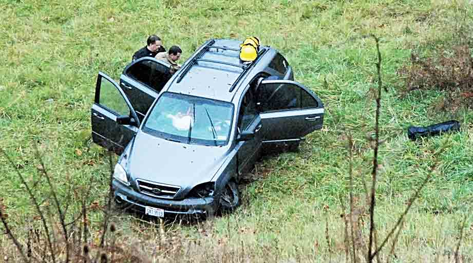 First responders work to assist young children in the backseat of an SUV that ran off of U.S. 50 Tuesday morning and slid about 150 feet down a hill. The children and their mother were taken by ambulance to Marietta Memorial's Belpre Campus, a Wood County Sheriff's deputy said. (Photo by Evan Bevins)
