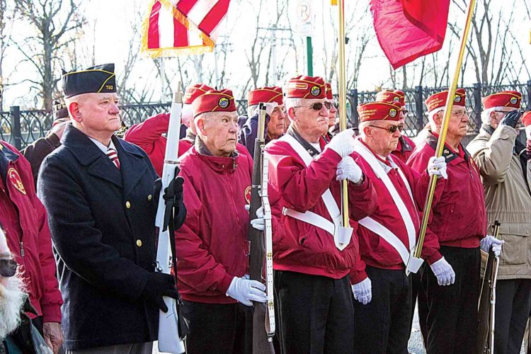 James Evans, 68, left, of Lowell, stands at attention alongside members of the Parkersburg-Marietta Marine Corps League during the Pearl Harbor Remembrance Day service at Muskingum Park Wednesday. (Photo by Janelle Patterson)