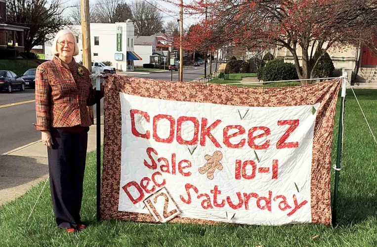 Photo Provided Linda Dally promotes Saturday's Cookeez sale at the First Lutheran Church, 19th and Plum streets. Dally made the quilt.