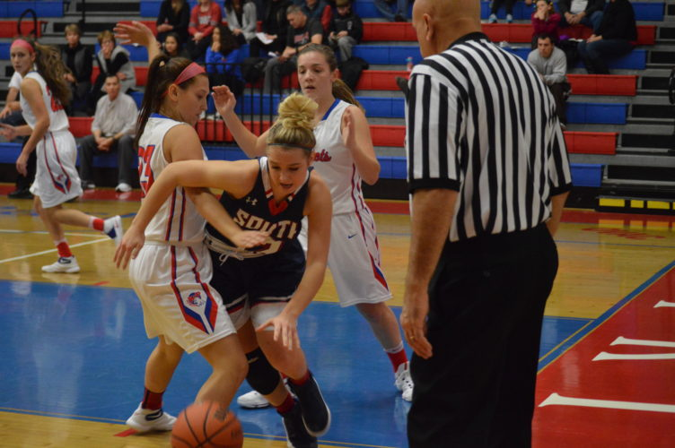 Photo by Josh Strope Parkersburg South's Lexi Moore (12) tries to get out of a trap by Wheeling Park's Kristin Hartman (23) and Laurel Robb during a high school basketball game Saturday.