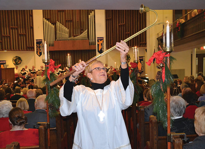 "Photo by Brett Dunlap Janet Ray lights processional candles during the annual performance of ""An Advent Celebration"" on Sunday at First United Methodist Church on Juliana Street."