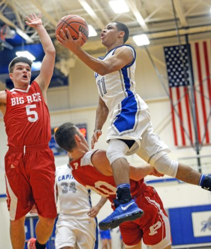 Capital's Leondre' Rogers goes up to the basket against Parkersburg's Karson Snyder (30) and Parker Miller (5). Photo by Chris Dorst, The Gazette-Mail.